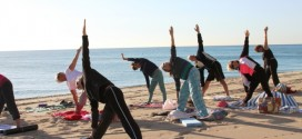 Participants practicing yoga on the beach.