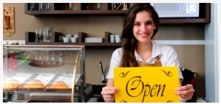 Business owner holding an open sign at her store