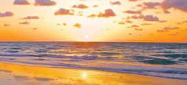view of the beach at sunrise with orange and purple sky over the ocean.