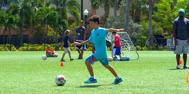Child plays soccer during Sports Camp.