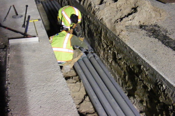 Photo: Utility Workers connecting underground pipes