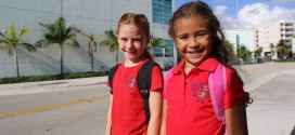 Photo of two young girls smiling in front of the NSE SIB K-8 School.