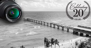 """A black and white photo of the Newport Pier in Sunny Isles Beach with a """"20 Year"""" symbol superimposed on top."""