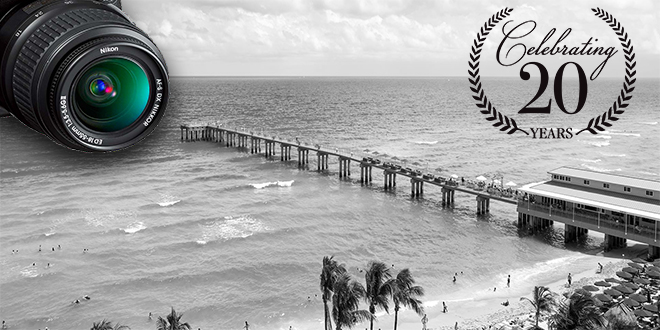 "A black and white photo of the Newport Pier in Sunny Isles Beach with a ""20 Year"" symbol superimposed on top."