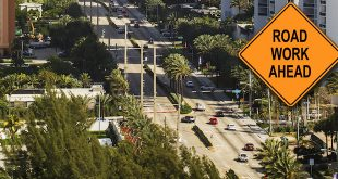 "An aerial view of Collins Avenue in Sunny Isles Beach with ""Road Work Ahead"" Sign superimposed on Top."