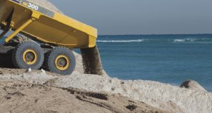 Photo of a construction machine hauling sand on the beach depicting beach renourishment.
