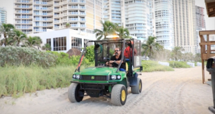 Photo of officials spraying for mosquitoes on the beach.