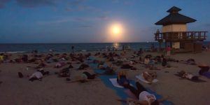 Full Moon Yoga participants laying on their yoga mats on the beach under a full moon.