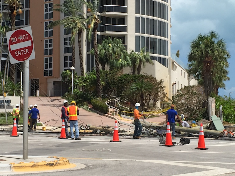 FPL crews work on power lines strewn across Collins Avenue.
