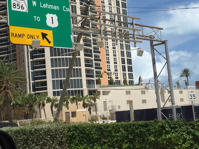 A power line post leans against William Lehman Causeway Ramp Signage in Sunny Isles Beach.