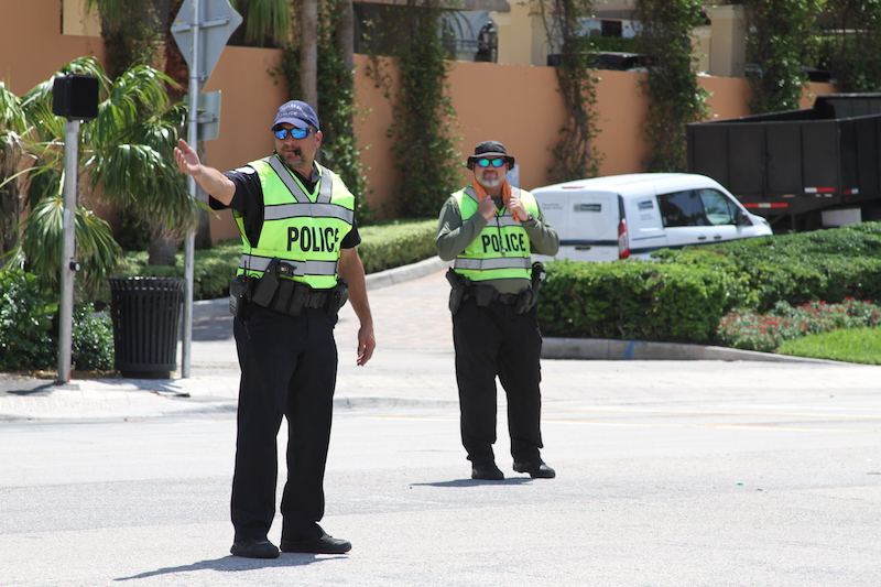 Police officer direct traffic in the hot sun.