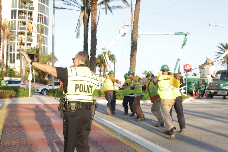 Sunny Isles Beach Police stop traffic as FPL crew run a powerline across the road, 5 days after Hurricane Irma.