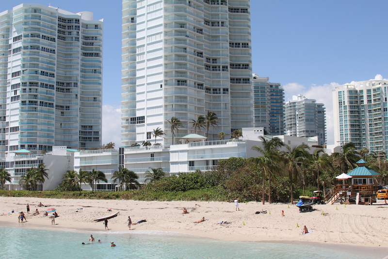 Beachgoers swim in the water while buildings behind them have hurricane shutters on their windows.