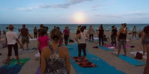 Residents practicing yoga on the beach as the full moon rises over the ocean.