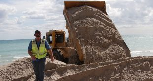 Dumptruck dumps sand on the beach during the Beach Sand Renourishment Project.