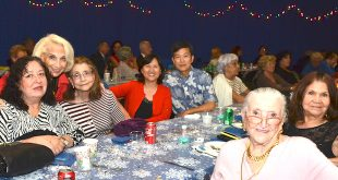 SIB Residents smile for the camera while sitting at a table at the City's Holiday Ball Party.