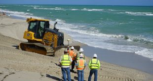 Workers and uniloader on the beach moving sand for the Beach Renourishment Project.