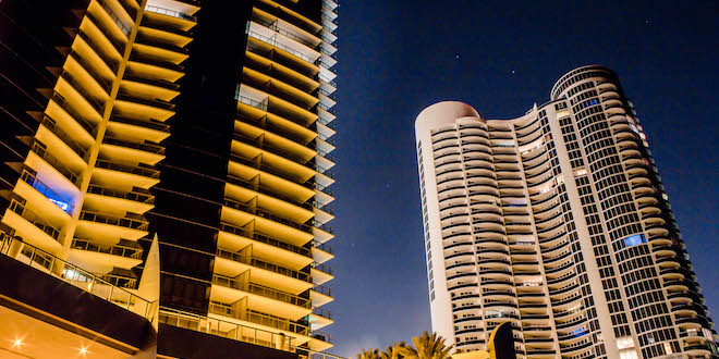 Two high-rise buildings lit up at night with a blue night sky background
