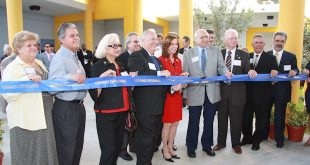 City officials stand in front of a ribbon during the Grand Opening of the NSE SIB K-8 School