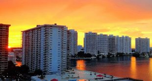 Condominiums on the intracoastal waterway at sunset with orange and yellow skies.