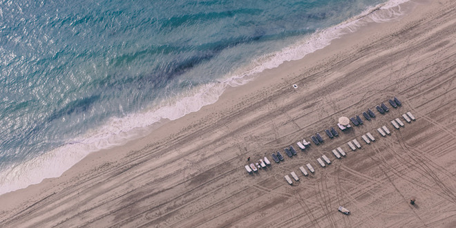 Aerial view of the neatly grated beach and shoreline with white beach chairs lined up.