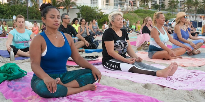 Full Moon Yoga class participants meditating on the beach