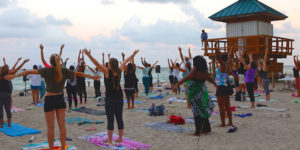 Yoga class participants on practicing on the beach.