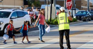 Mother and her two children cross the street on the way to school with crossing guard holding a stop sign for traffic.