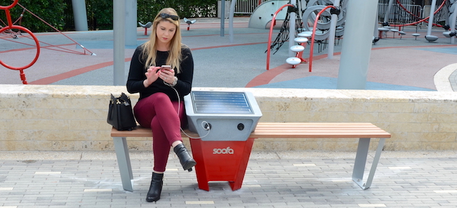 Woman using a Soofa smart bench, looking at her phone.
