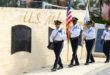 Veterans Day Color Guard carrying flags in front of Heritage Park Veterans Wall