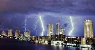 Two lightning strikes from dark clouds at nighttime above the city skyline of Sunny Isles Beach.