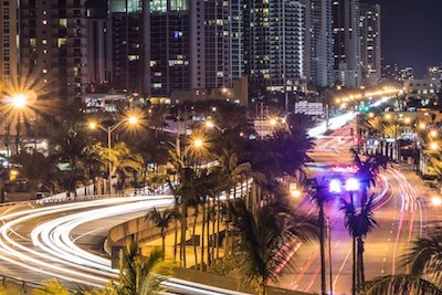 Photo: Collins Avenue lit up by street lights and traffic lights at nighttime.