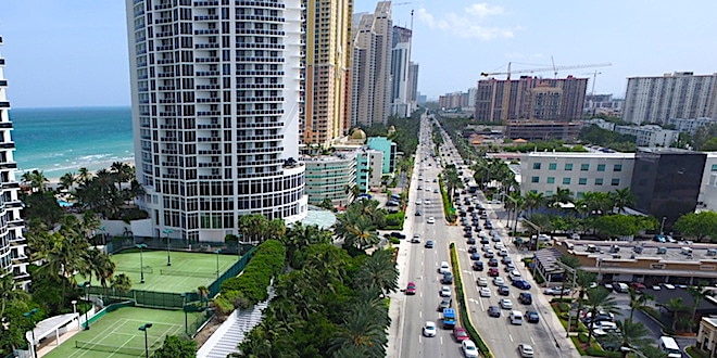 Traffic on Collins Avenue in Sunny Isles Beach with buildings and ocean view of coastline.