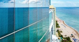 Building Reflecting Ocean in Side Glass Paneling