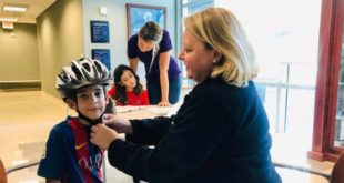 Sandra Block fits a young boy with a free bicycle helmet.