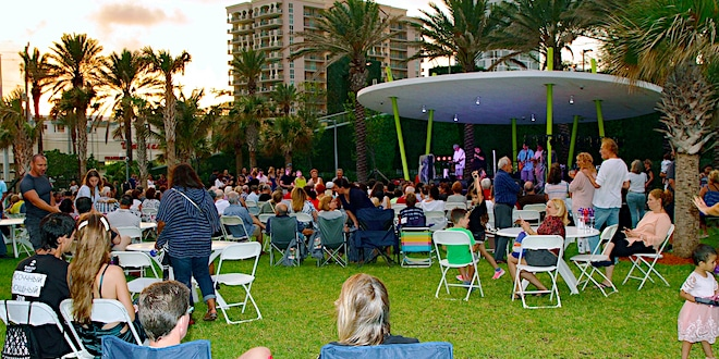 Audience in lawn chairs at Samson Oceanfront Park as they watch a live concert.
