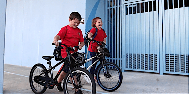 Two students walking their bicycles to the racks as they arrive at school