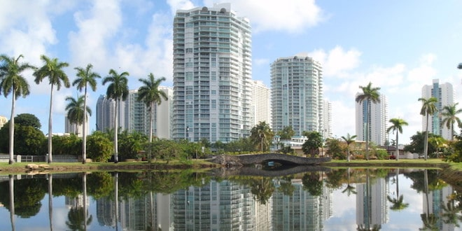 Sunny Isles Beach high rises reflect off waterway.