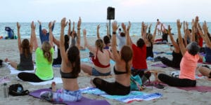 Class participants stretching during Full Moon Yoga on the Beach