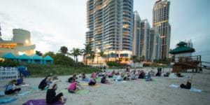 Yoga participants stretching to the side as they sit on yoga mats during class on the beach.