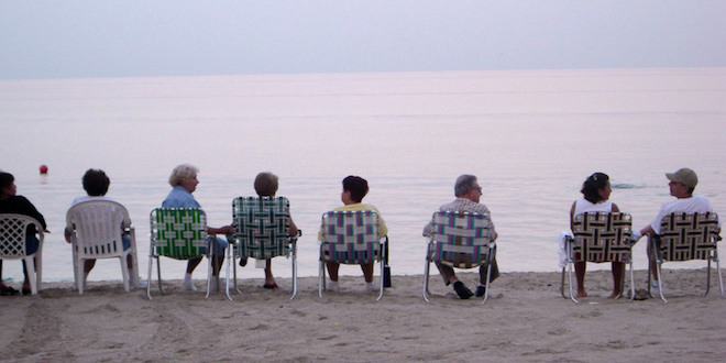 Seniors sitting in a row of lawn chairs on the beach facing the ocean.