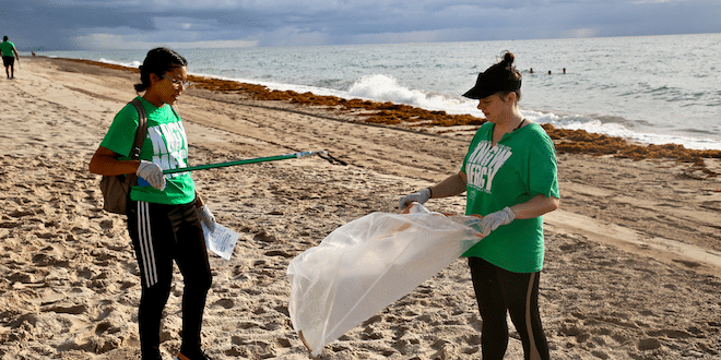 Volunteers cleaning up trash on the beach during a Sunny Isles Beach Beach Cleanup event