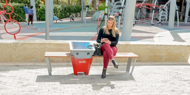Patron using solar-powered bench charging station at City park