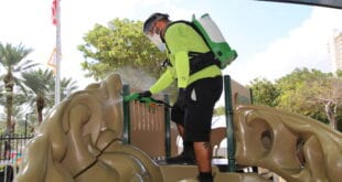 Parks staff sanitizing playground equipment