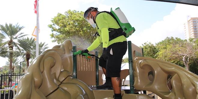 Parks staff sanitizing playground equipment