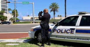Police officer clocking speeders on Collins Avenue