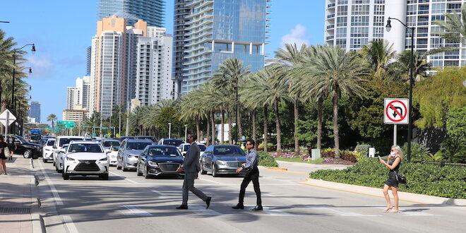 Pedestrians crossing Collins Avenue using a crosswalk.