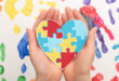 woman holding heart with puzzle on white with hand prints for World Autism Awareness
