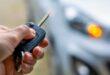 Hand holding a key fob locking a car