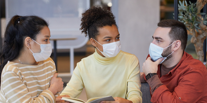 Group of people wearing masks while working at a table together in a cafe.